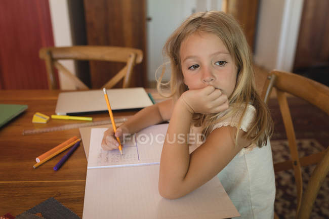 Thoughtful girl doing her homework at home and looking away, hand on chin — Stock Photo