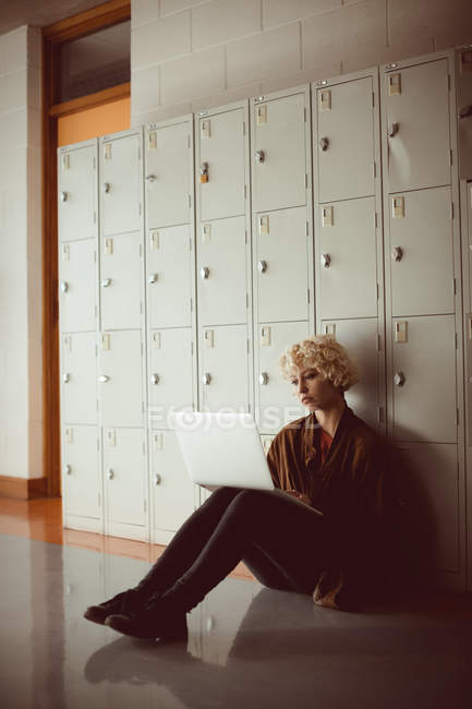 Mujer joven usando portátil en vestuario en la biblioteca sentado en el suelo - foto de stock