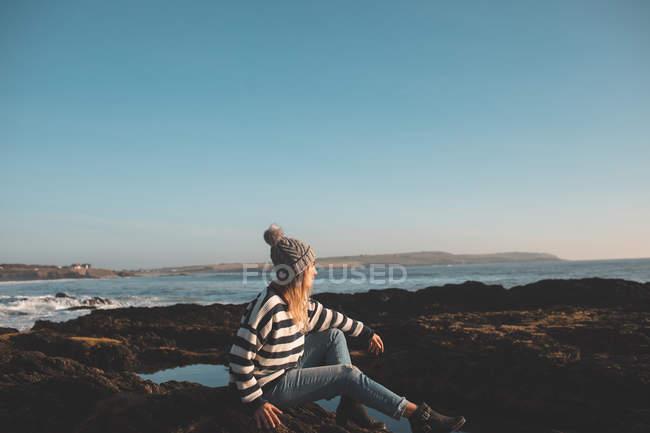Donna premurosa seduta sulla roccia in spiaggia — Foto stock