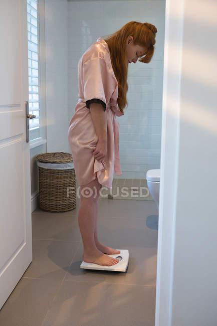 Donna che controlla il suo peso sulle bilance a casa — Foto stock