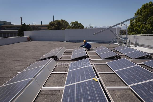 Trabalhador do sexo masculino trabalhando na estação solar em um dia ensolarado — Fotografia de Stock