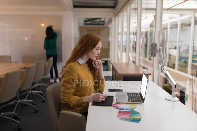Female graphic designer using graphics tablet in office — Stock Photo