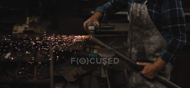 Schmied schleift Metallstange mit Schleifmaschine in Werkstatt — Stockfoto