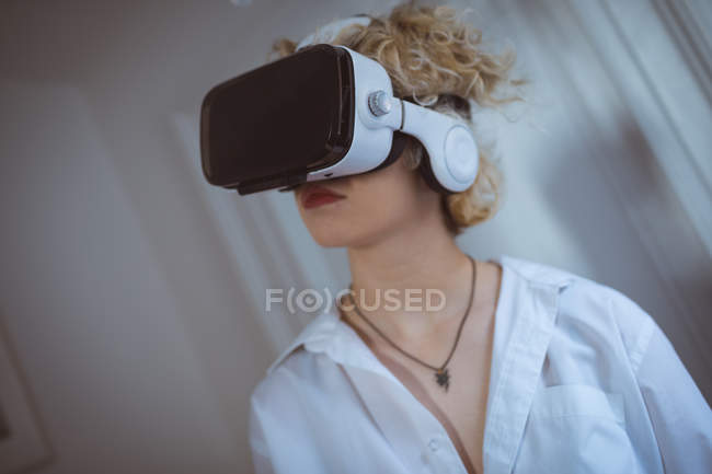 Young woman using virtual reality headset at home — Stock Photo