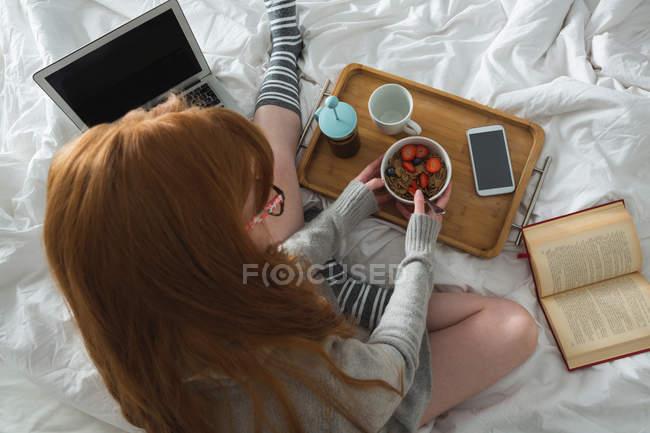 Женщина завтракает в спальне дома — стоковое фото