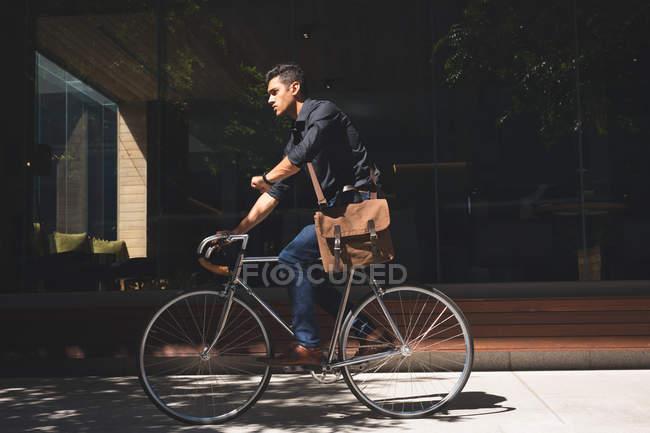 Jovem empresário verificando o tempo durante o ciclismo em instalações de escritório — Fotografia de Stock