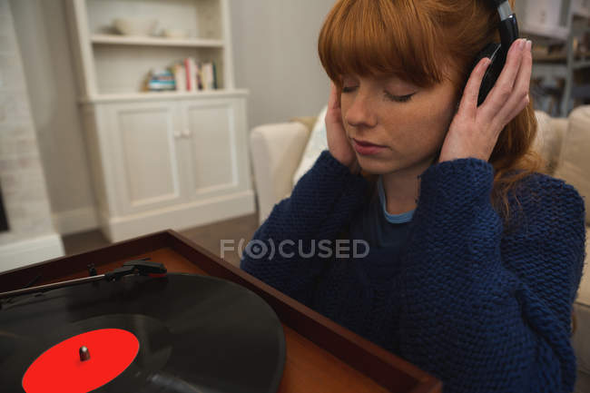 Woman in headphones listening to music on gramophone at home — Stock Photo