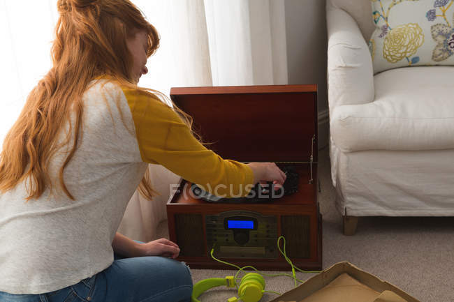 Rear view of woman playing a gramophone at home — Stock Photo