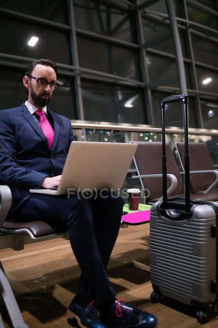 Businessman using laptop in waiting area at airport — Stock Photo