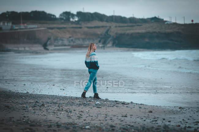 Donna premurosa che cammina su una spiaggia — Foto stock