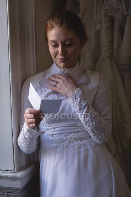 Jeune mariée en robe de mariée lisant une note à la boutique — Photo de stock