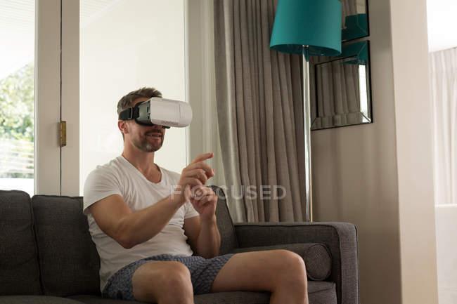 Людина за допомогою віртуальної реальності гарнітуру у вітальні на дому — стокове фото