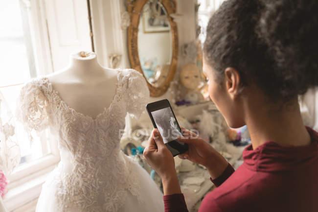 Femme métissée prenant des photos de robe de mariée sur téléphone portable en boutique — Photo de stock
