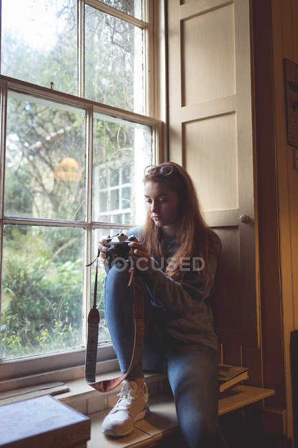 Woman reviewing pictures on retro camera near window at home — Stock Photo
