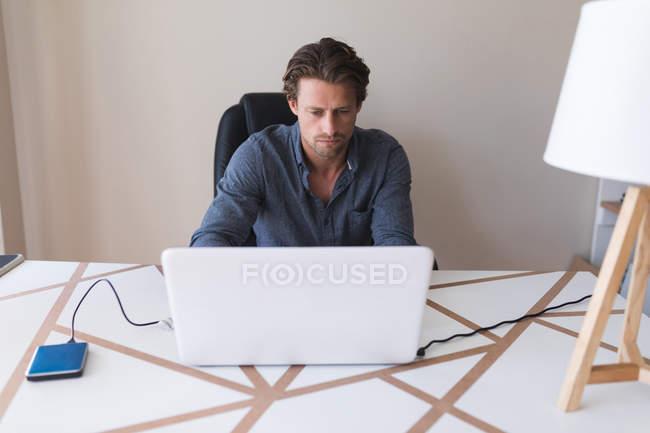 Homem atento usando laptop em casa — Fotografia de Stock