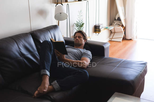 Man reading a book in living room at home — Stock Photo