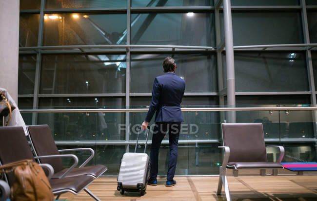 Rear view of businessman waiting at waiting area at airport — Stock Photo