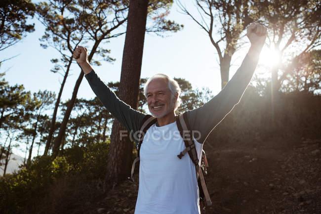 Старший турист, стоящий с оружием в лесу за городом — стоковое фото