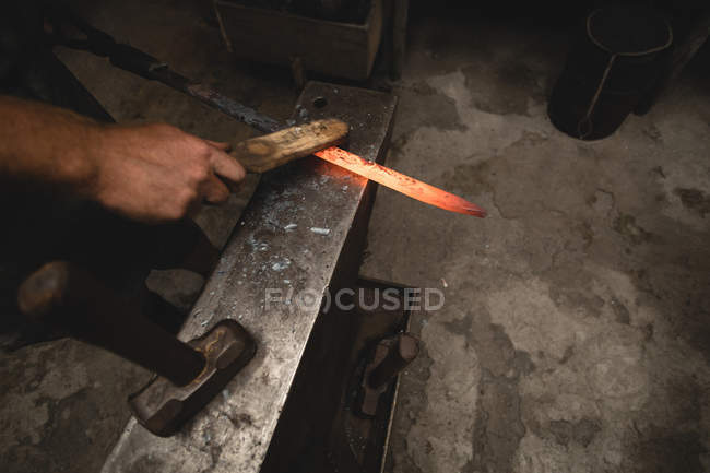 Blacksmith examining a hot metal rod in workshop — Stock Photo
