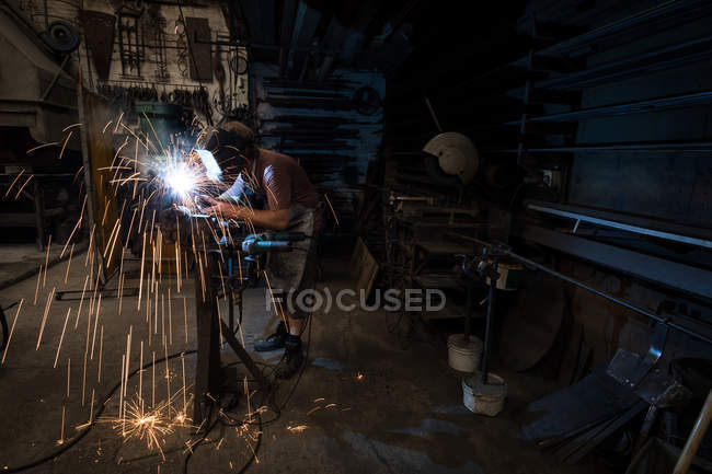 Blacksmith using a welding torch in workshop — Stock Photo