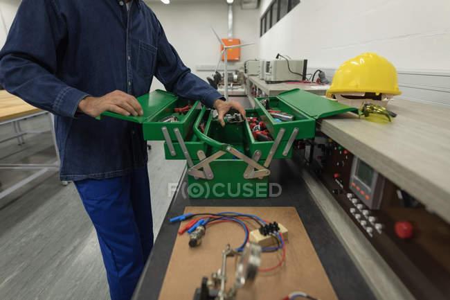 Arbeiter entfernt Werkzeug aus Werkzeugkiste im Büro — Stockfoto