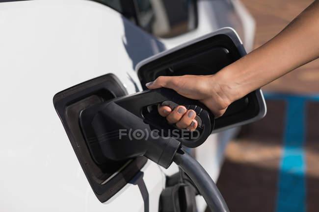 Gros plan de la femme rechargeant une voiture électrique à la station de recharge — Photo de stock