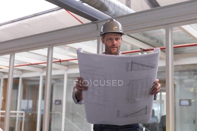 Чоловічий архітектор, дивлячись на blueprint в офісі — стокове фото