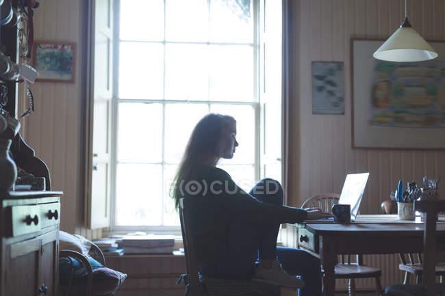 Giovane donna che utilizza il computer portatile a casa — Foto stock