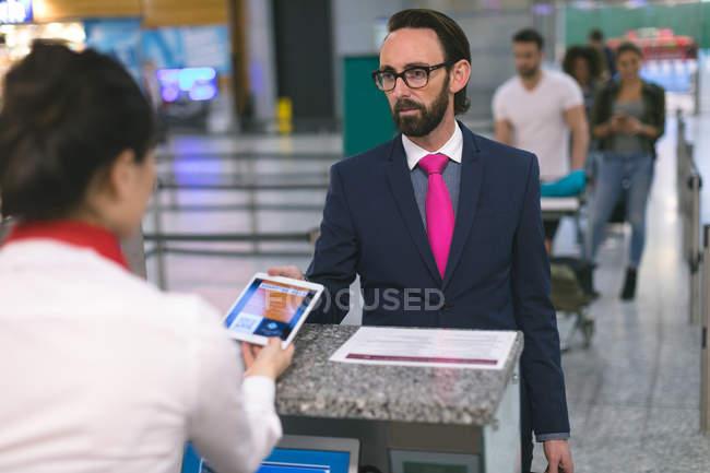 Companhia aérea entrada atendente verificar a passagem do viajante de bilhete mensal na tablet digital no aeroporto — Fotografia de Stock