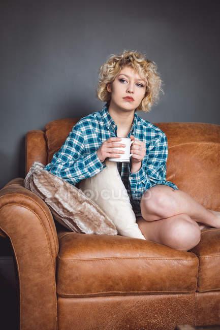 Задумчивая женщина пьет кофе в гостиной дома — стоковое фото
