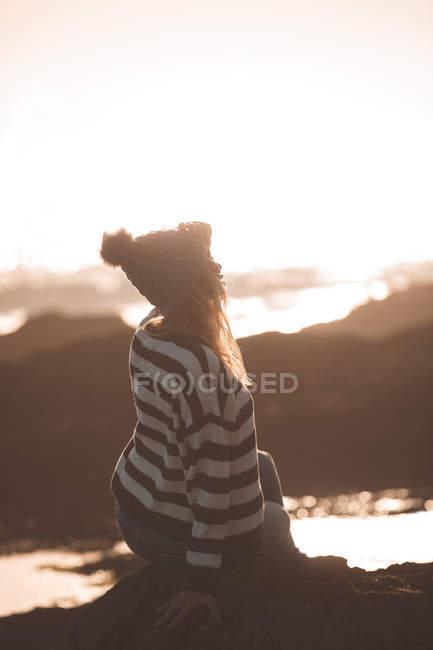 Thoughtful woman sitting on rock at beach — Stock Photo
