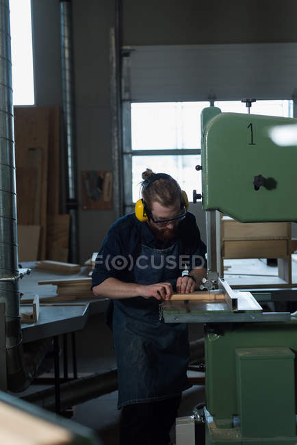 Male carpenter using vertical cutter machine at workshop — Stock Photo