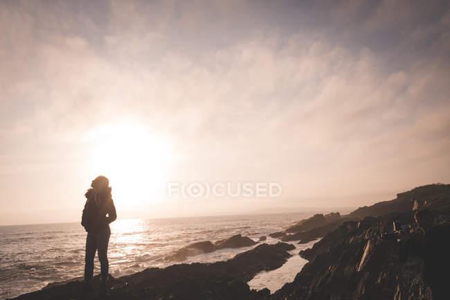 Silhouette di donna in piedi su una spiaggia al crepuscolo — Foto stock