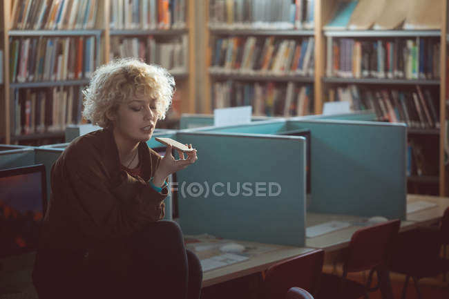 Giovane donna che comunica sul cellulare in biblioteca — Foto stock