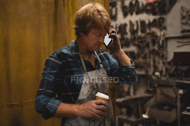 Blacksmith talking on the phone in workshop — Stock Photo