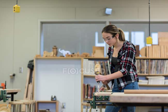 Жіночий Карпентер, використовуючи долото з молотом на шматок дерева на семінарі — стокове фото