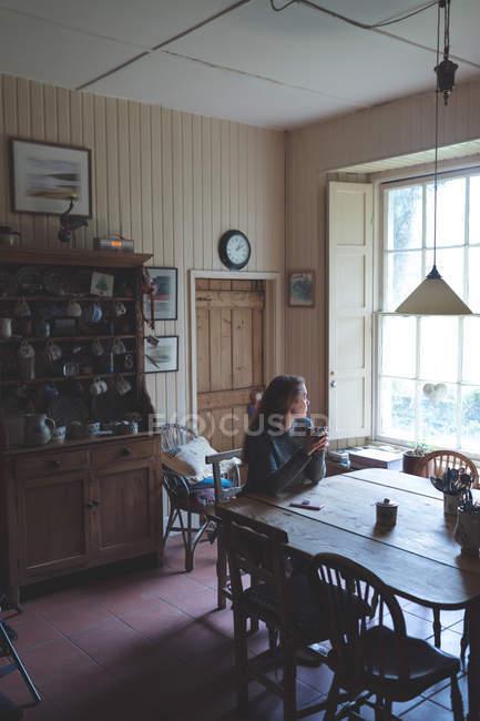 Задумчивая женщина пьет кофе дома — стоковое фото