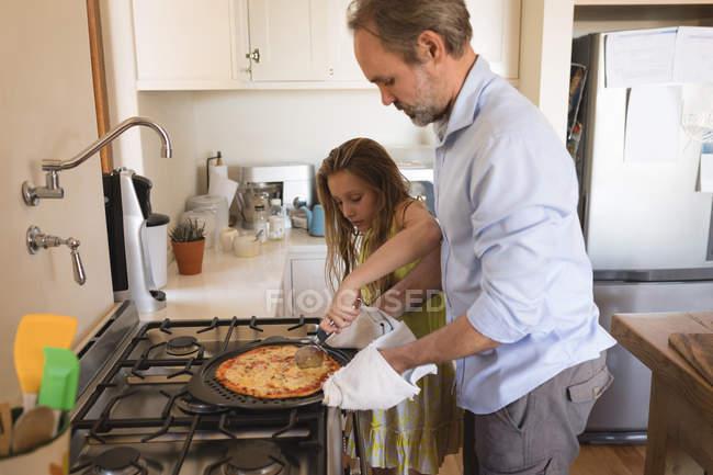 Pai e filha preparar pizza na cozinha em casa — Fotografia de Stock