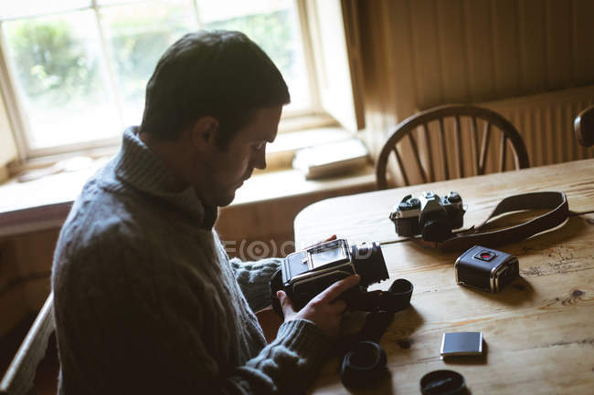 Attentive man repairing a camera at home — Stock Photo