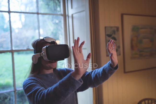 Жінка використовує шолом віртуальної реальності вдома. — стокове фото