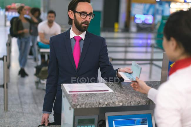 Línea aérea llegadas asistente dar pasaporte al viajero en mostrador en la terminal del aeropuerto - foto de stock