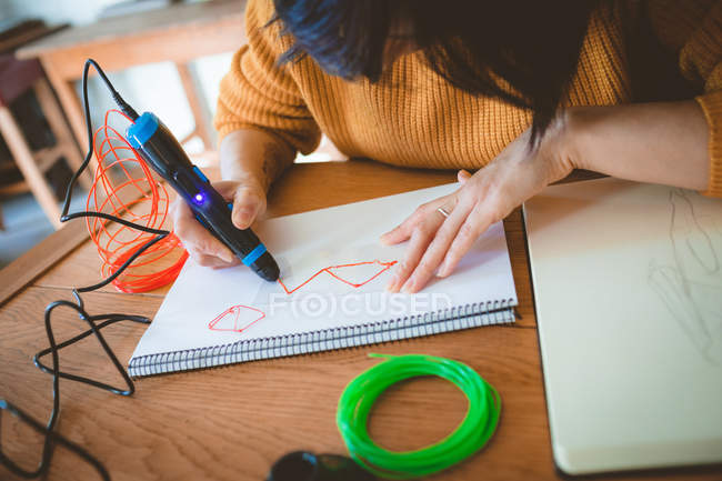 Woman using electric pen for drawing a sketch at home — Stock Photo