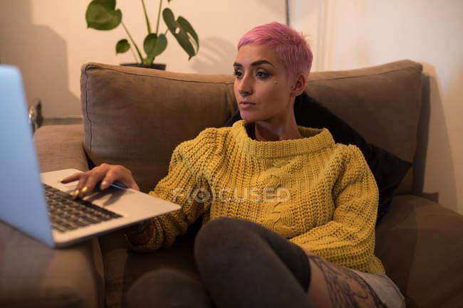 Стильною жінкою, використовуючи ноутбук у вітальні на дому — стокове фото