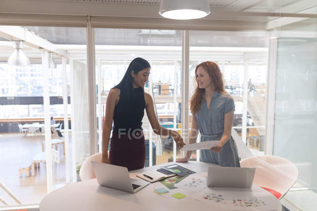 Female executives discussing over document in office — Stock Photo
