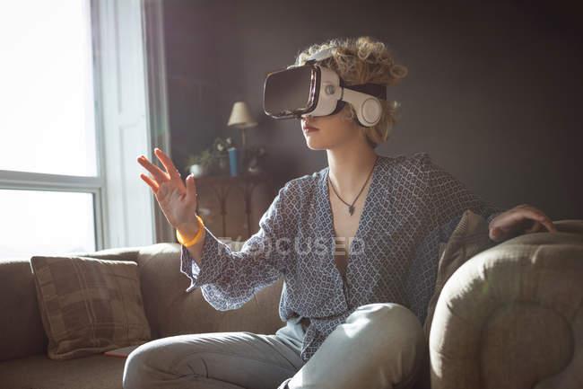 Frau nutzt Virtual-Reality-Headset im heimischen Wohnzimmer — Stockfoto