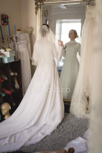 Caucasian bride in wedding dress and veil looking into mirror at vintage boutique — Stock Photo