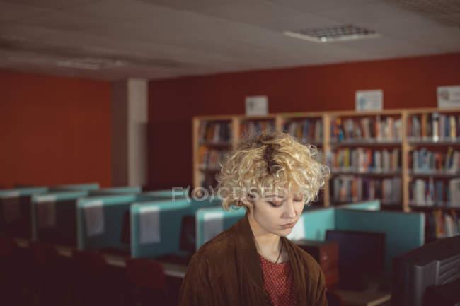 Jeune femme réfléchie debout dans la bibliothèque — Photo de stock