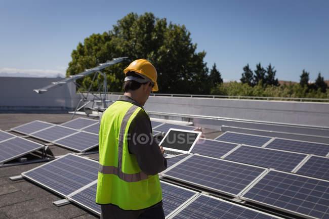 Мужчина работает с ноутбуком на солнечной станции в солнечный день — стоковое фото