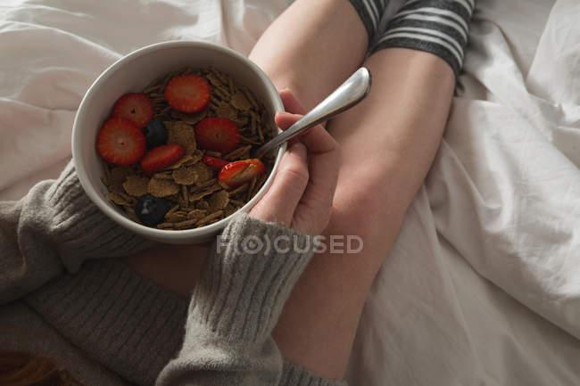 Femme tenant bol de petit déjeuner dans la chambre à coucher à la maison — Photo de stock