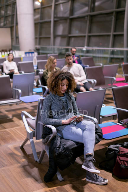 Woman using mobile phone in waiting area at airport — Stock Photo